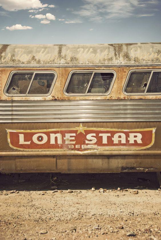 A retro foto of a midcentury Lone Star beer ad on the side of an old abandoned bus