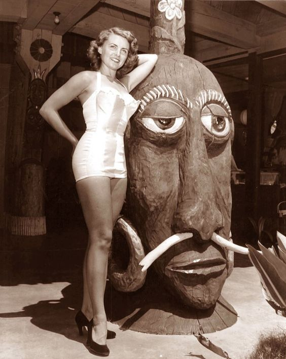 A vintage foto showing a woman in a forties one-piece bathing suit posing in a tiki style cocktail bar