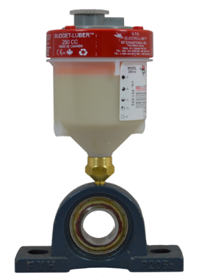 Image of electro-luber on bearing stand. The single point lubricator is filled with white food safe grease.