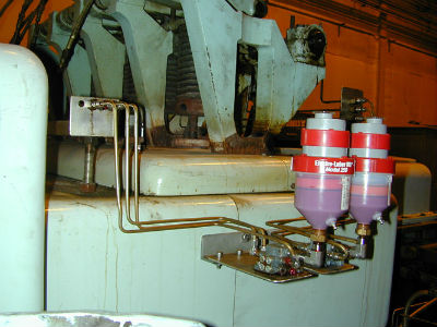 Two motor driven, automatic lubricators attached to distribution blocks to feed multiple ports consistent lubrication