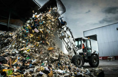 Digger truck unloading garbage and rubbish at a municipal dump