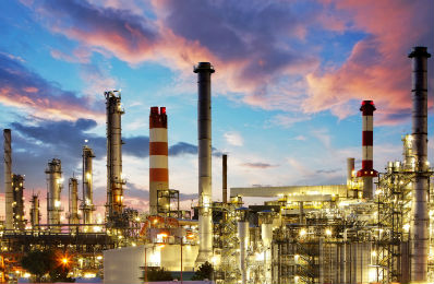 Image of a petrochemical plant illuminated against a dusk sunset.
