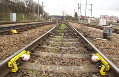 Two electro-lubers attached to the lube points on the rails of a train track