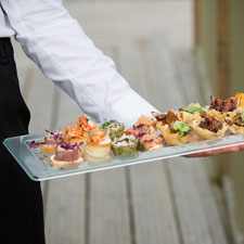 langley larder staff serve canapes at a wedding